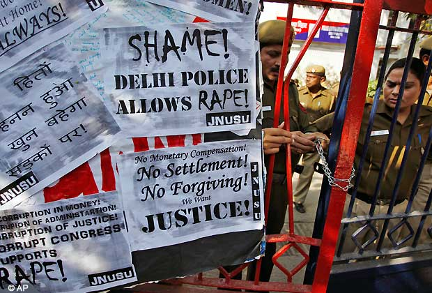 Indian police officers lock the gate of the police station during a protest condemning the gang rape of a 23-year-old student on a city bus late Sunday in New Delhi, India, Tuesday, Dec. 18, 2012. The Indian parliament Tuesday witnessed outrage over the issue even as the victim is battling for her life at a city hospital. (AP Photo/Tsering Topgyal)