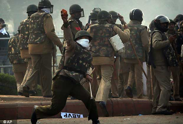 An Indian police officer throws back stones at protesters during a violent demonstration near the India Gate against a gang rape and brutal beating of a 23-year-old student on a bus last week, in New Delhi, India, Sunday, Dec. 23, 2012. The attack last Sunday has sparked days of protests across the country. (AP Photo/Saurabh Das)