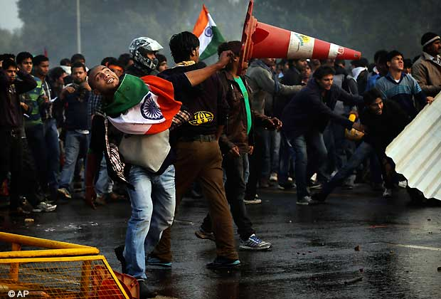 A protester throws a traffic cone at Indian police during a violent demonstration near the India Gate against the gang rape and brutal beating of a 23-year-old student on a bus last week, in New Delhi, India, Sunday, Dec. 23, 2012. The attack last Sunday has sparked days of protests across the country. (AP Photo/Kevin Frayer)