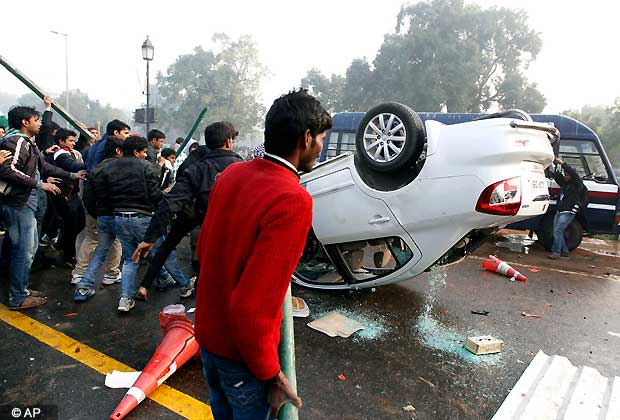 Indian protestors damage a government vehicle during a violent demonstration near the India Gate monument against the gang rape and brutal beating of a 23-year-old student on a bus last week, in New Delhi, India, Sunday, Dec. 23, 2012. The attack last Sunday has sparked days of protests across the country. (AP Photo/Mustafa Quraishi)
