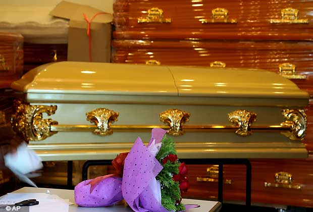 A bouquet of roses are left in front of the empty coffin for the body of a young Indian woman who was gang-raped in Delhi, on Saturday Dec. 29, 2012 in Singapore. (AP Photo/Wong Maye-E)