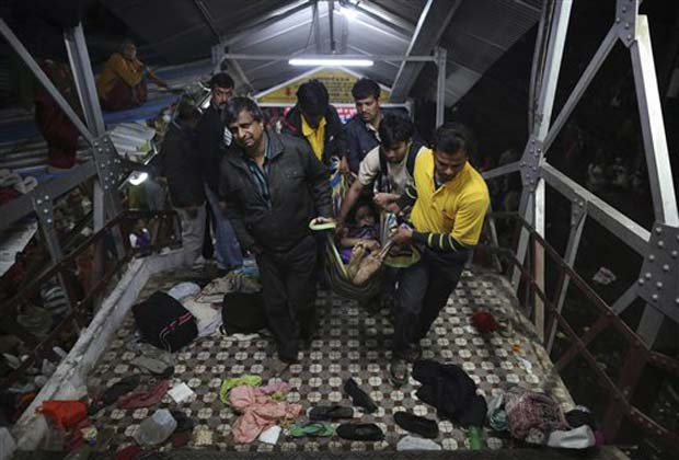 Indian men carry the body of a woman killed in a stampede on the railway platform where the incident occurred at the main railway station in Allahabad, India, Sunday, Feb. 10, 2013.(AP Photo)