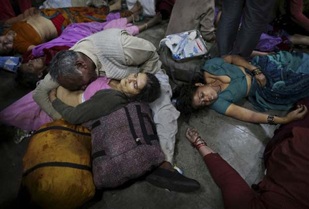 An Indian man weeps as he holds his wife who was killed in a stampede on a railway platform as other bodies are seen beside at the main railway station in Allahabad, India, Sunday, Feb. 10, 2013.(AP Photo)