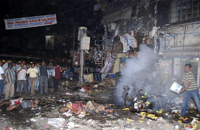 EDS NOTE GRAPHIC CONTENT - Bodies of victims lie on the ground after a bomb blast in Hyderabad, India,Thursday, Feb.21, 2013. At least 11 people were killed and 50 injured Thursday in a pair of explosions in a crowded area of the southern Indian city of Hyderabad, officials said. (AP Photo)