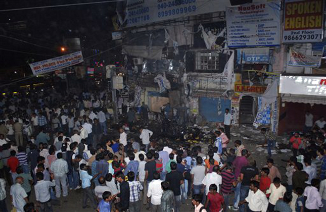 People gather on the scene after a bomb blast in Hyderabad, India,Thursday, Feb. 21, 2013. At least 11 people were killed and 50 injured Thursday in a pair of explosions in a crowded area of the southern Indian city of Hyderabad, officials said. (AP Photo)